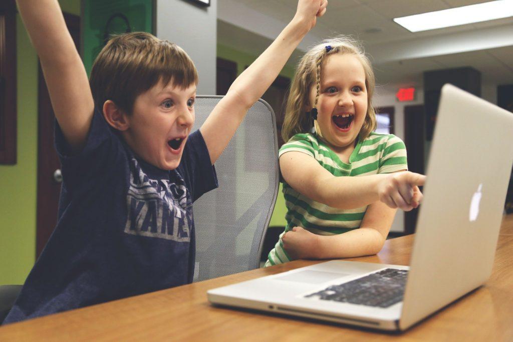 パソコンに向かって喜ぶ子供たち